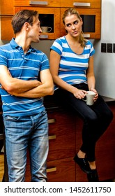 Young married couple in love drinking tea or coffee in the kitchen during the morning breakfast.