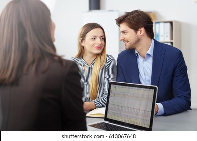 Young married couple in a meeting with a broker or agent sitting looking at each other smiling as they reach a decision