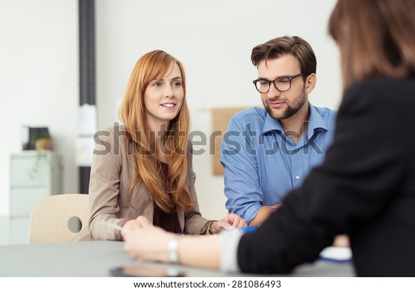 Young married couple in a meeting with a broker or agent with focus to the attractive redhead wife