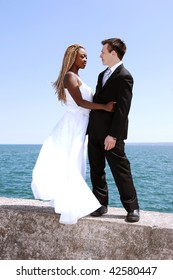 An young married couple on a photo shoot at the Hamilton harbor standing on a concrete wall with the lake Ontario in the background.