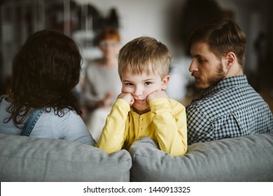 Young married couple with son during family therapy with counselor