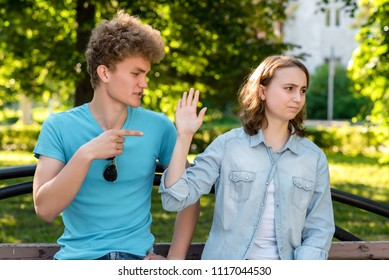 Young married couple. In the summer in the park in nature. The guy scolds the girl. Emotions of mistrust. Insults and insults in the relationship. Problems in family life. Concept scandal behavior.