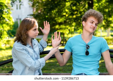 Young married couple. In the summer in the park in nature. The girl rebukes the guy. Emotions of mistrust. Insults and insults in the relationship. Problems in family life.