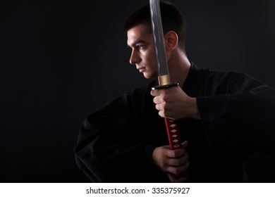 Young martial arts fighter with katana on black background
