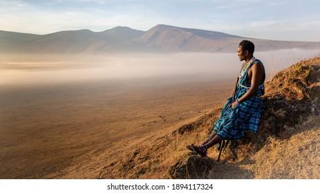 Young Masai Warrior sitting inside the crater of Ngorongoro park watching sunrise