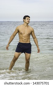A young masculine guy, half naked,  is standing on the water of the beach, looking forward./on the beach