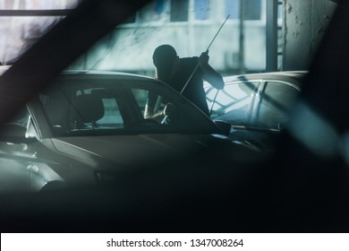 Young masked thief is robbing a car with pry bar in bright daylight in the parking lot