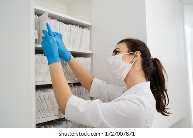 A young masked woman doctor reads case history in an archive at a modern hospital