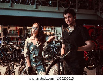Young master and his attractive apprentice are taking a break after repairing a bicycle at workshop.