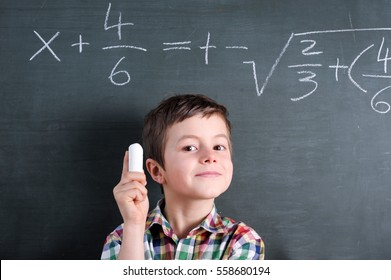 Young math genius in front of blackboard with mathematical problem and chalk in his hand