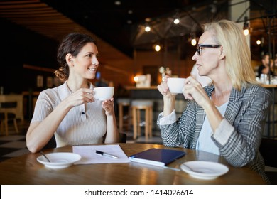 Young and mature businesswomen in smart casual sitting by table in front of each other, having coffee and discussing ideas or strategies