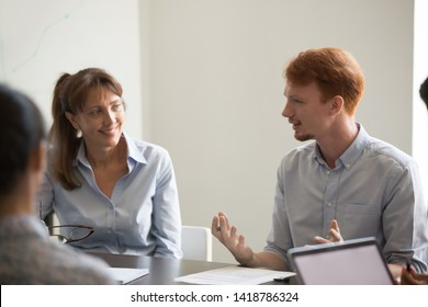 Young and mature colleagues discussing common goals new project sitting in boardroom at company meeting, listening business coach redhead team leader. Concept of staff training, mentoring and teamwork