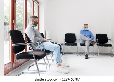 Young and mature man with face masks sitting in a waiting room of a hospital or office - focus on the young man