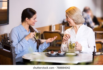 Young and mature woman drinking tea and talking in coffee-house and smiling