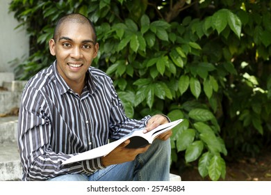 Young Mauritian, Indian & African looking man reading a book outdoors