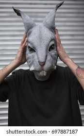 young mean wearing a scary rabbit mask holding his hand with his hands