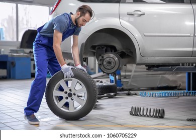 Young mechanic with car tire in service center
