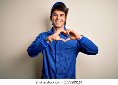 Young mechanic man wearing blue cap and uniform standing over isolated white background smiling in love doing heart symbol shape with hands. Romantic concept.
