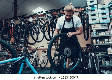 Young Mechanic Repairs Bicycle in Bike Workshop. Portrait of Bearded Man Wearing White T-Shirt and Apron Examines and Fixes Modern Cycle. Bike Maintenance and Sport Shop Concept