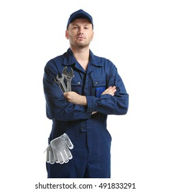 Young mechanic in uniform with a wrench and gloves in pocket, isolated on white
