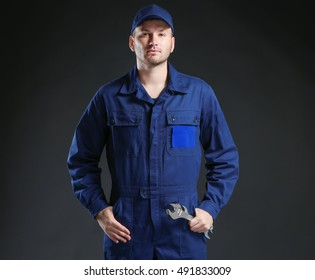 Young mechanic in uniform with a wrench standing on a black background