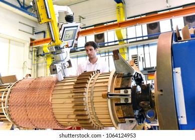 young mechanical engineering workers operate a machine for winding copper wire - manufacture of transformers in a factory