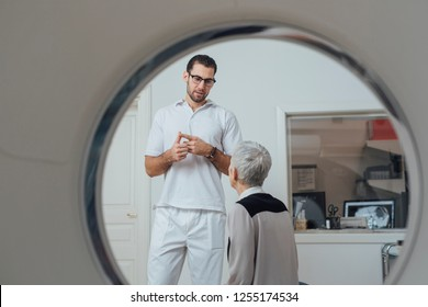 Young medical technician talking to senior patient next to a CT scan mashine.