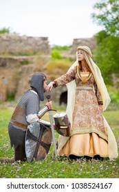Young medieval knight and lady on green grass outdoor in springtime.