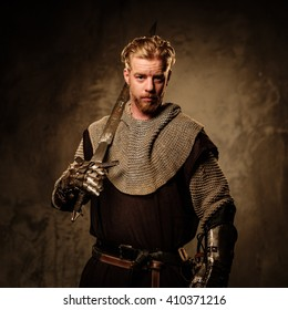 Young medieval knight posing on dark background.