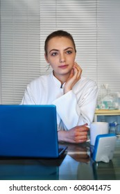 Young medtech, doctor or practitioner drinks coffee in front of working laptop in her office.
