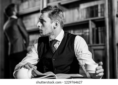 Young men with antique bookshelves on background. Educated elite or aristocrats spend leisure in library. Intelligent, man in suit with good manners hold cup of tea. Aristocrats and elite concept.