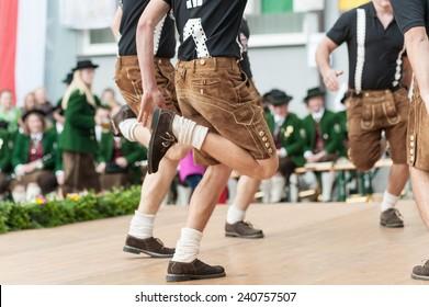 Junge Männer, die einen austrianischen traditionellen Volkstanz machen