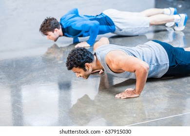 young men doing push-up at sports center
