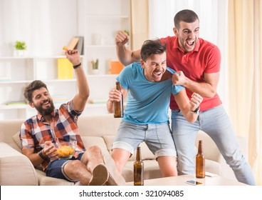 Young men drink beer, eat pizza and cheering for football