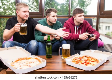 Young men drink beer, eat pizza and play video games  at home