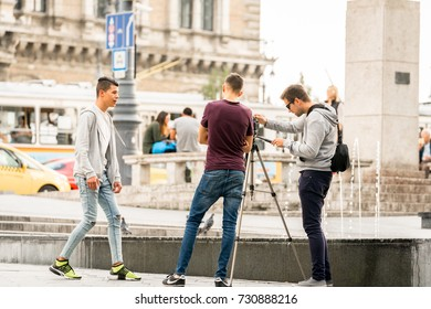 Young men filming. Budapest, Hungary - September 27, 2017: Three young males just completed filming each other after skateboarding at a city square in Budapest. Traffic and people in the background.
