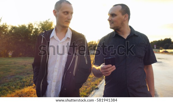 Young men have a serious talk while walking in the city during beautiful sunset. Looking at mobile phone businessman showing something about new project