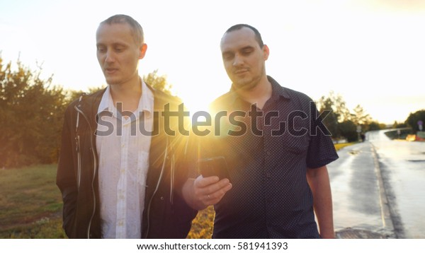Young men have a serious talk while walking in the city during beautiful sunset with lense flare effects. Looking at mobile phone businessman showing something about new project, their work