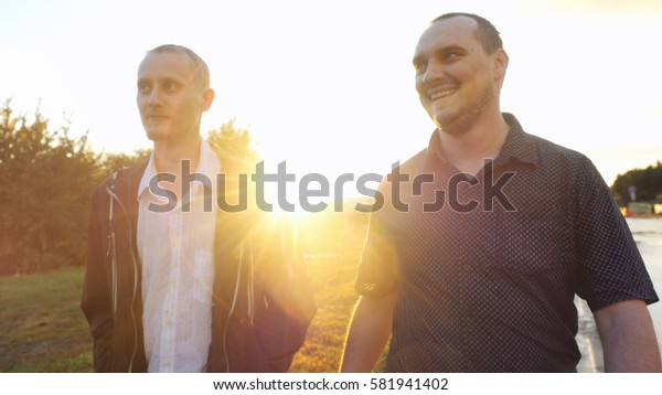 Young men have a serious talk while walking in the city during beautiful sunset with lense flare effects