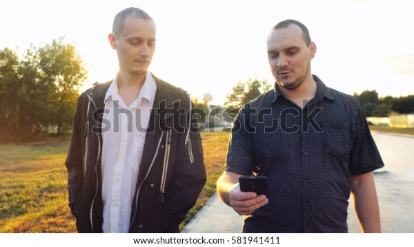 Young men have a serious talk while walking in the city during beautiful sunset with lense flare effects. Looking at mobile phone businessman showing something about new project