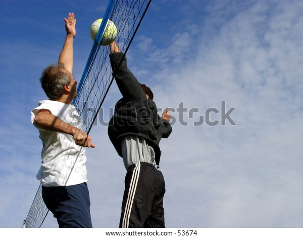 Young men hitting the ball over the net