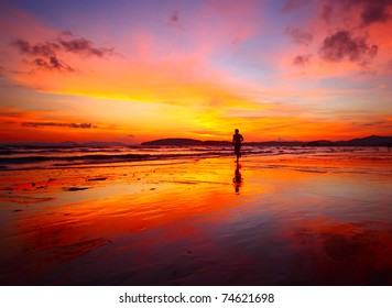 Young men jogging on wet sand by sea edge on vivid sunset background