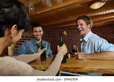 Young men laughing at woman drinking beer in pub.?