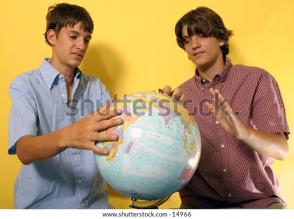 young men looking at globe