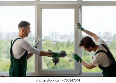 Young men mounting a window section into the frame. Team of professional workers, window replacement in the apartment.