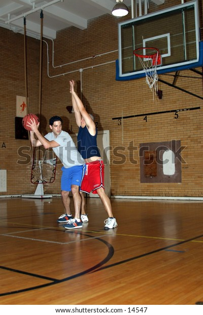 young men playing indoor basketball