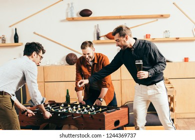 young men playing table soccer together in cafe