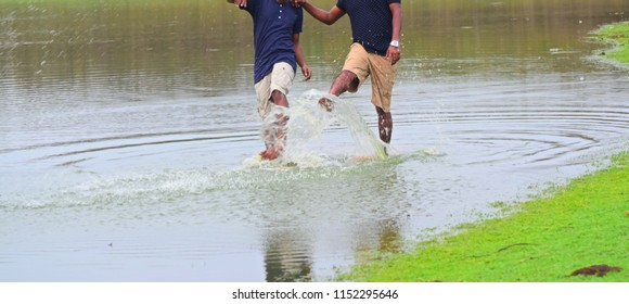 Young men playing together with lake water isolated unique blurry photo