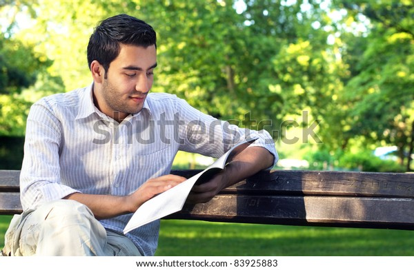 Young men reading book in a park