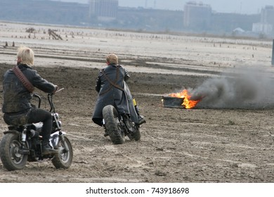 young men riding motorcycles near the fire
